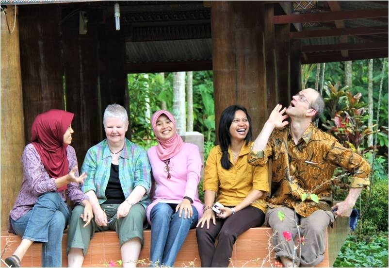 Members of ICEH's LINKS Programme sit on a bench, joking with each other