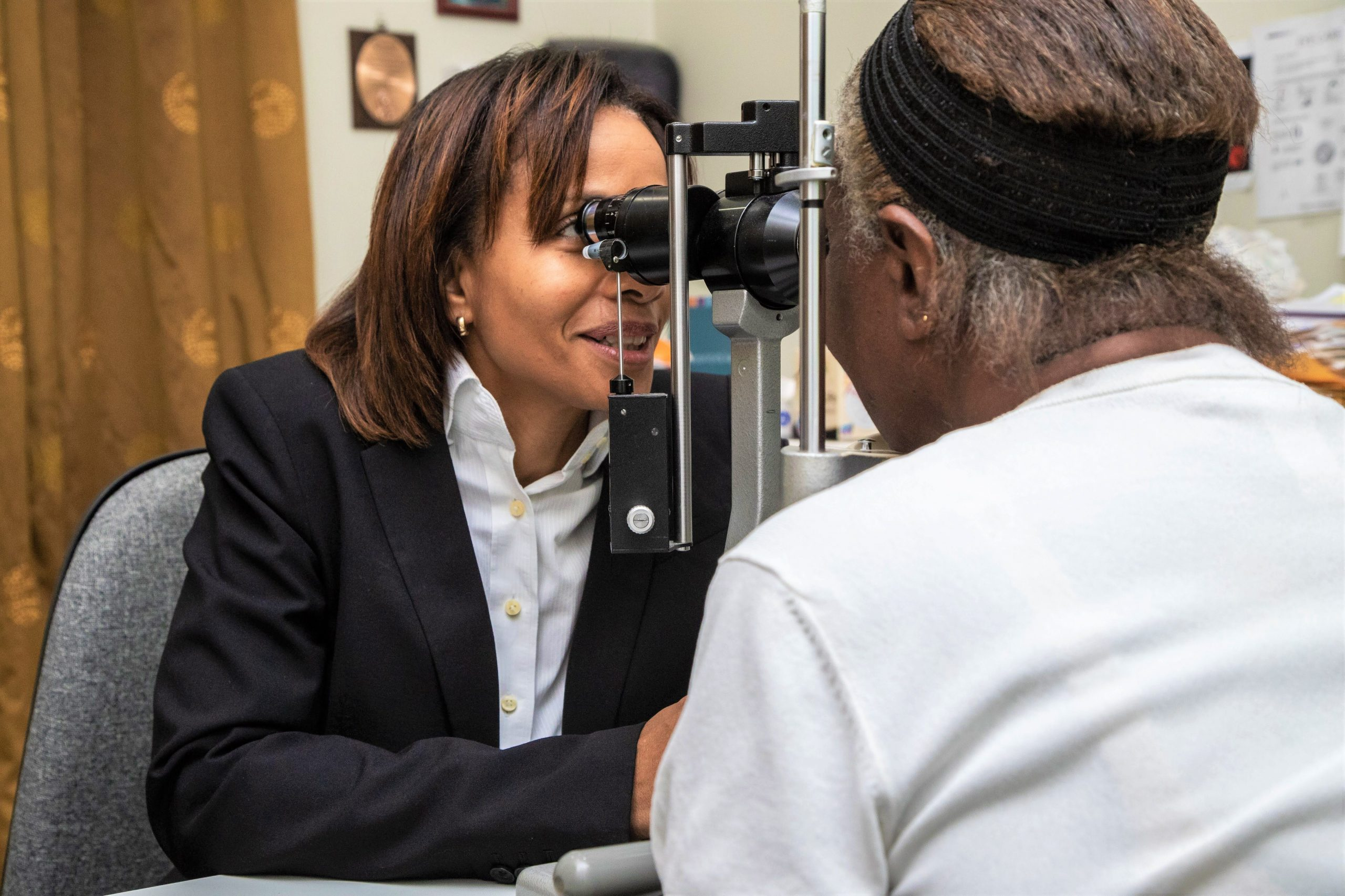 An opthalmologist inspects a patient's eye with a slit lamp
