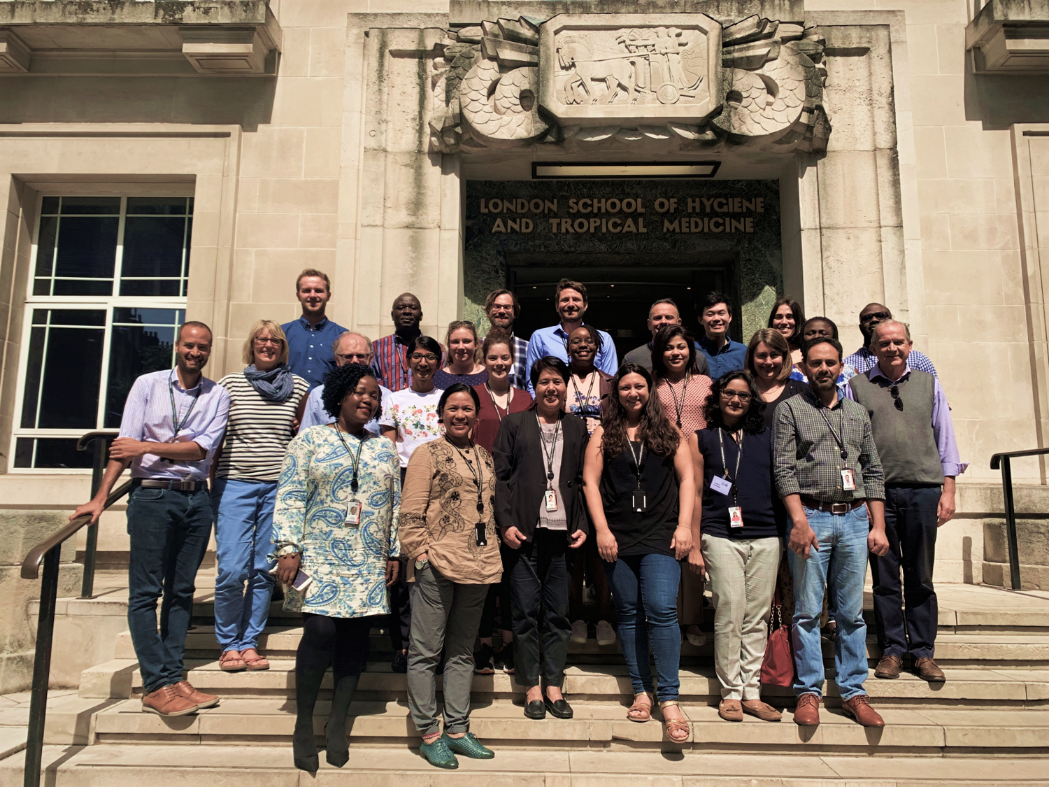 Attendees of the ICEH short course stand smiling on the steps of the school
