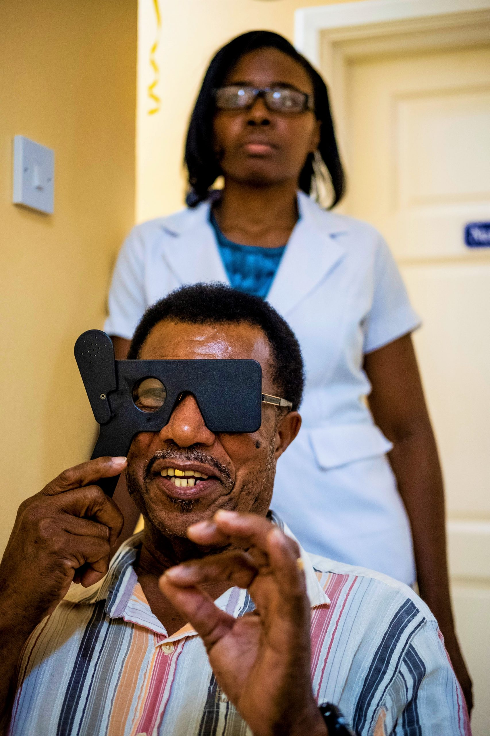 A man in St. Lucia  checks his vision through a portable phoropter